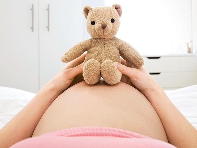 Bauch einer Schwangeren mit Teddy