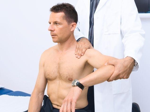 Mann mit Arzt bei Schulteruntersuch