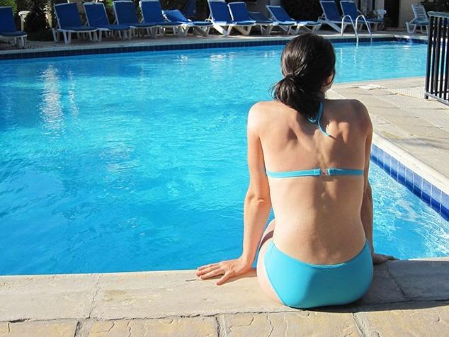 Frau in Badekleidung am Schwimmbad sitzend