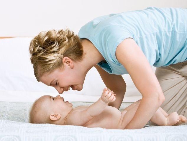 Mami mit Baby auf Bett
