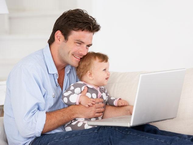 Papi mit Baby und Laptop
