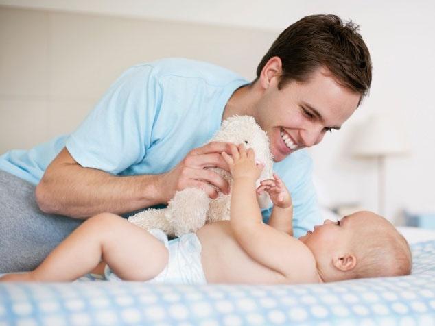 Papi mit Baby auf Bett