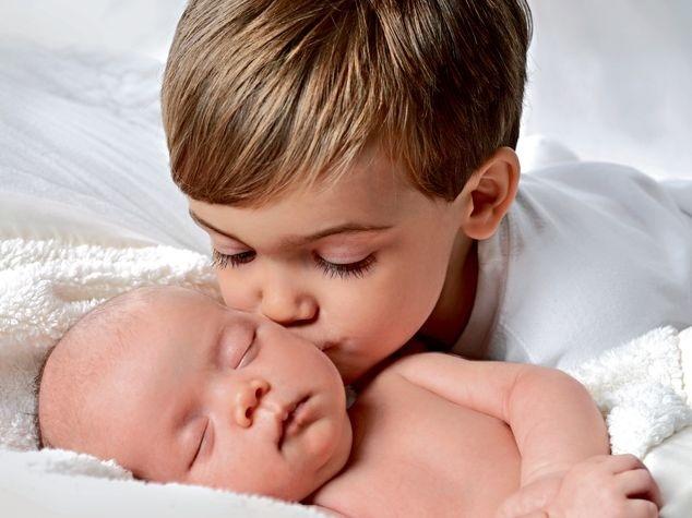 Geschwister küsst Baby