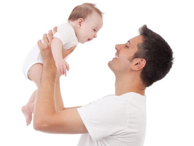 Papi hält Baby hoch.