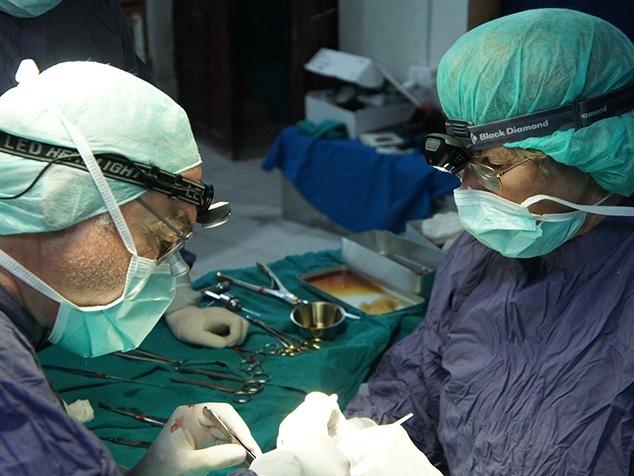 Ärzte mit Stirnlampen am Operieren