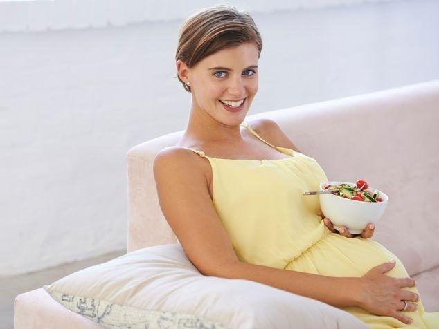 Frau mit Salatschüssel auf dem Bauch