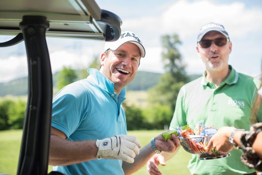 Golfer mit Snack in der Hand