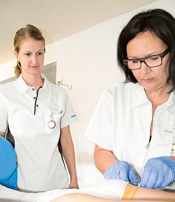 Physiomitarbeiterin beobachtet Pflegefachfrau