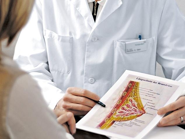 Arzt erklärt Patientin Brustschema
