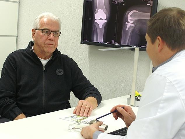 Artz im Gespräch mit Patient betreffend Knieprothese