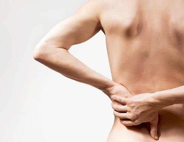 Person mit Rückenschmerz fasst sich an Rücken.