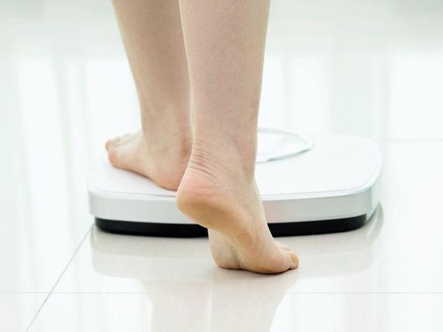 Person auf Waage misst ihr Körpergewicht