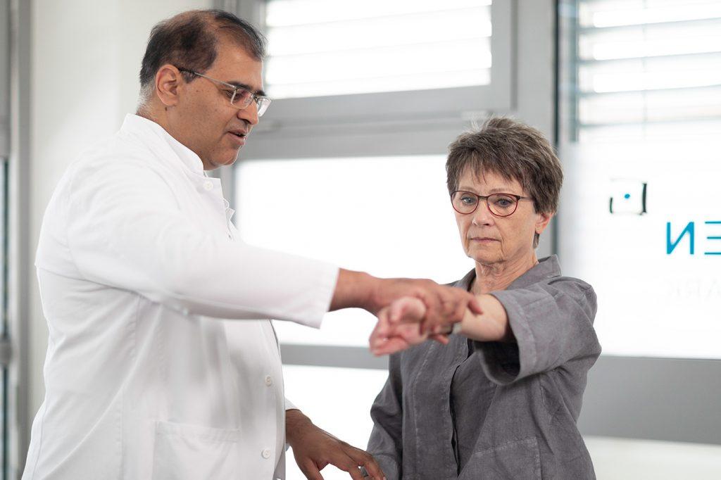 Patientin nach Schultersehnenriss bei Übung mit Arzt