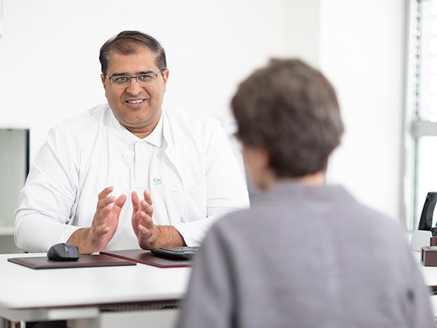 Arzt im Gespräch mit Patientin aufgrund Rotatorenmanschettenruptur