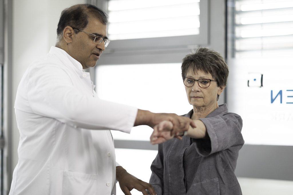 Arzt macht Übung mit Patientin mit Rotatorenmanschettenruptur