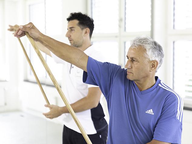 Physio und Patient bei Übung mit Schulterprothese