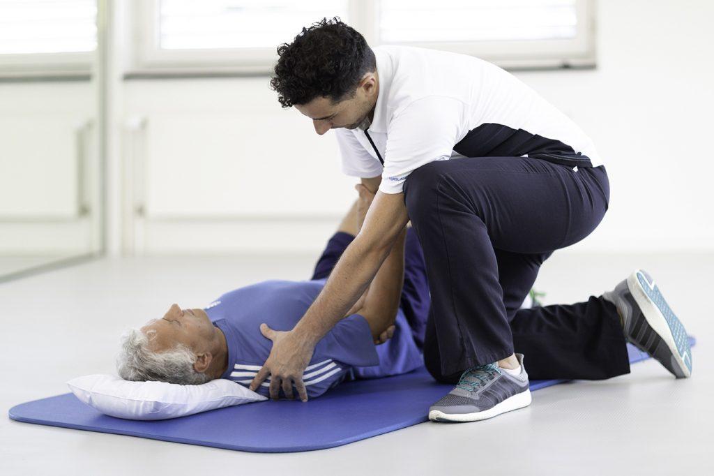 Patient und Physiotherapeut bei Übung mit Schulterprothese
