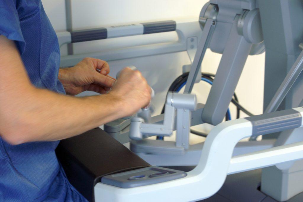 Le chirurgien dirige les instruments à l'aide des manettes de la console.