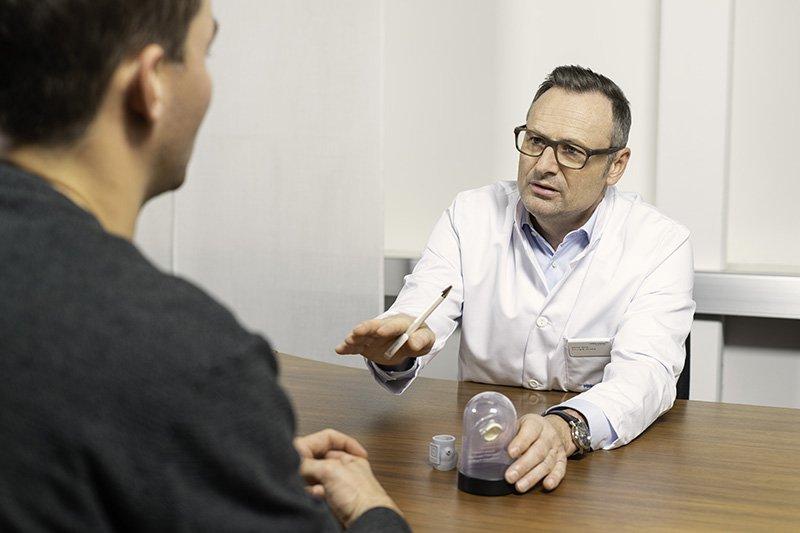 Arzt in Gespräch mit Patient vor Herzoperation