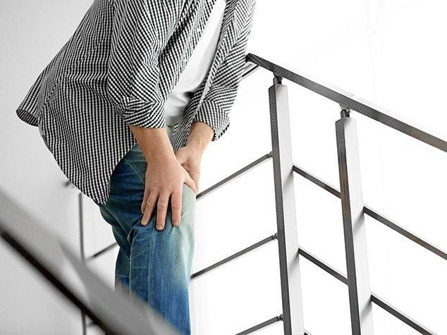 Mann hält sich Knie auf Treppe - ist er zufrieden mit seiner Knieprothese?