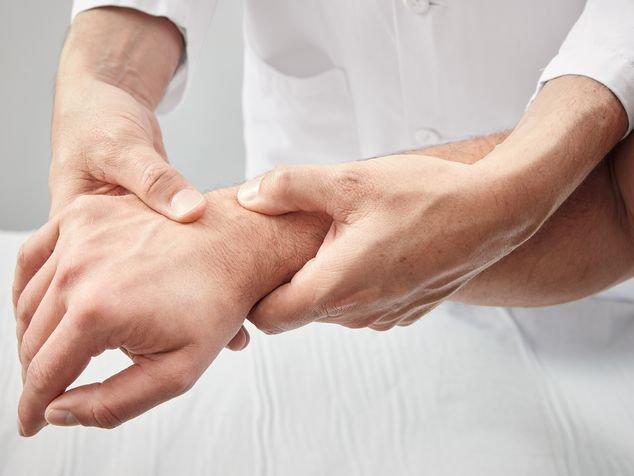 Sehnenscheidenentzündung, Arzt kontrolliert das Handgelenk
